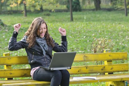 hand movements: happy young lady enjoying studying on a bench in park