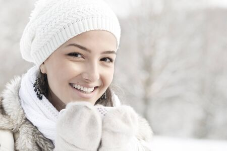 Head portrait of beautiful young woman smiling, holding cup of hot drink outside in winter. high key photo