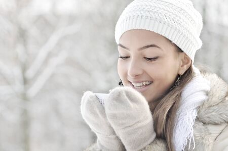 Head high key portrait of beautiful happy young woman smiling, holding cup of hot drink, outdoor, winter photo
