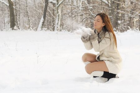 young woman blows snow flakes from open hands to the copy space Stock Photo - 8723573