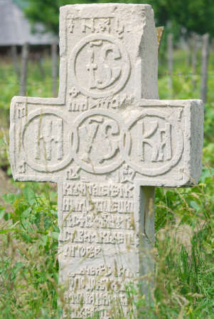 cyrillic: ancient orthodox crucifix stone with cyrillic signs in green area