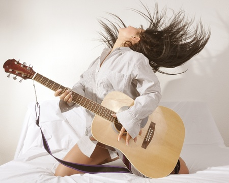 single woman: portrait of a girl is feeling free and playing guitar in a room