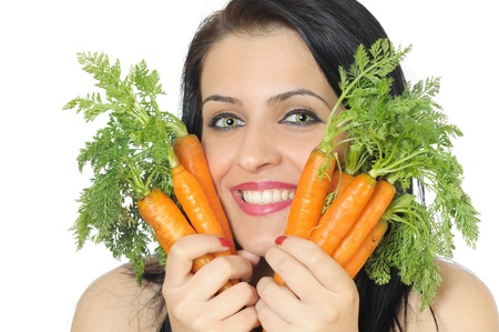 face of a young woman holding fresh carrots closed to her face