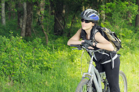 young biker woman getting rest in forest area and looking at copy space