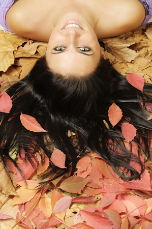 Beautiful smiling girl laying down on red-brown leaves Stock Photo