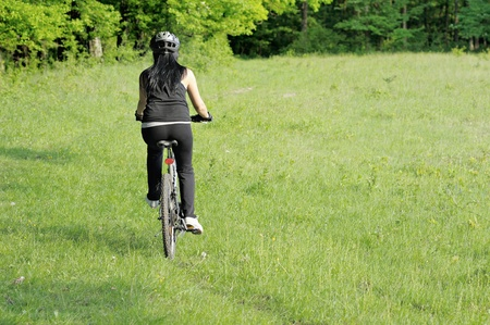 back of an woman riding a bicycle in green environment Stock Photo
