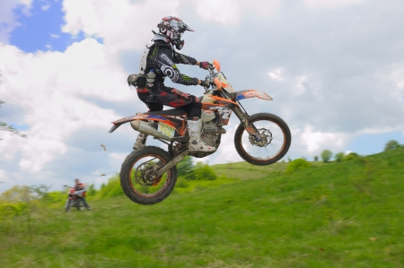 GHELARI, ROMANIA - MAY 5 2012: Norbert Levente JOZSA in action, jumping with his KTM bike, at hard enduro race  Editorial