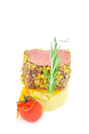 closeup view of prepared tenderloin with rosemary and a red tomato