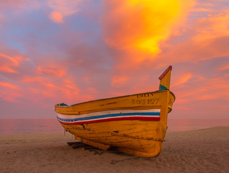 sunup: Boat stranded on the beach, sunset Stock Photo