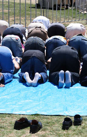 A group of muslims praying outdoors