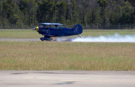 bi: Bi plane used for acrobatics - smoke being pumped out - taking off