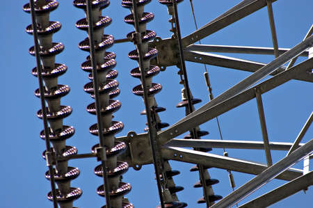 insulators: A closeup of an electrical pylon showing cables and insulators