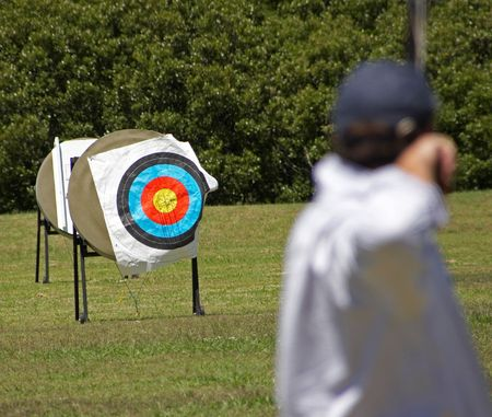 An archer (out of Focus) aiming at a bullseye target (in focus)
