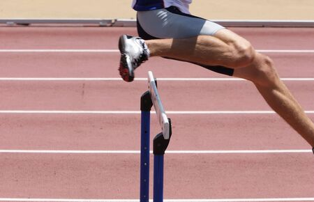 An athlete leaping the hurdles Standard-Bild