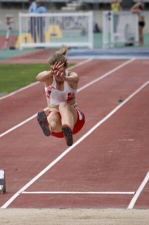 Athlete performing a long jump Standard-Bild