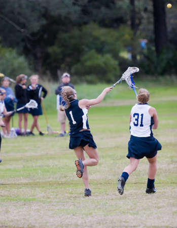 Two lacrosse players going for the ball