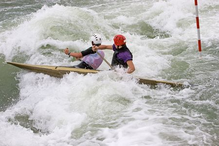 Two canoeists paddling through white water