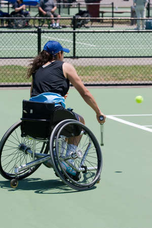 A wheelchair bound athlete on the tennis court about to hit a ball
