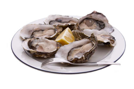 Oysters in the shell, lemon and fork on a plate - isolated