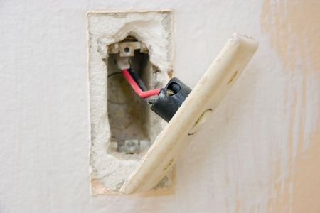 An old light switch hanging off the wall