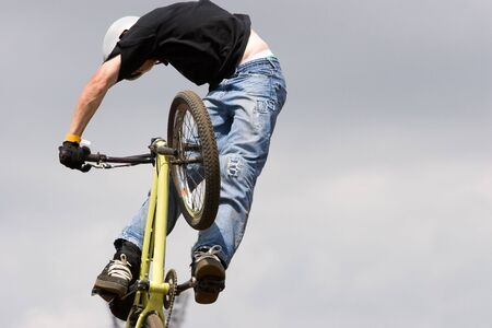 A BMX (Bicycle Moto-cross(X)) in the air against a clouded sky
