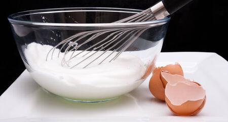 Egg whisk in a bowl with Egg whites and broken egg shells against a black background