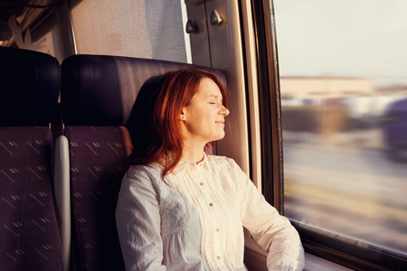 Traveling Comfort -Young woman sleeping feeling relaxed traveling  in the train. Stock Photo