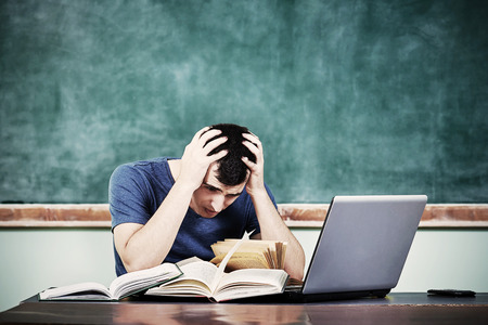 Sad upset overworked man studying in front of  stack of books with a blackboard behind him.