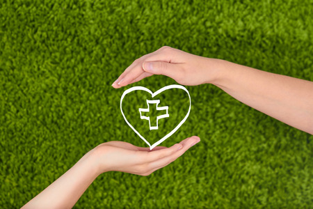 Woman hands holding heart isolated on green background. Family health, charity and medicine concept.