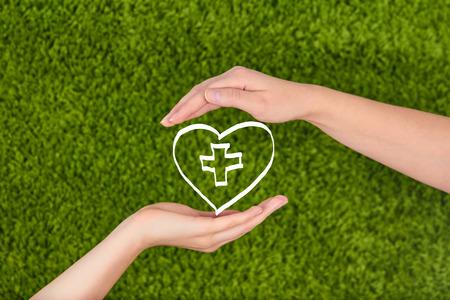 dando la mano: Manos de mujer sosteniendo el corazón aislado en fondo verde. Salud de la familia, la caridad y el concepto de la medicina.