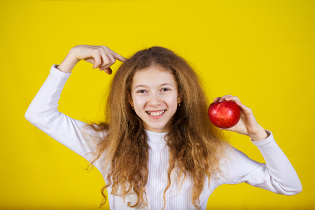 Happy, smiling little girl holding an red apple, pointing with finger to her head isolated on yellow background.Healthy food,Healthy Thinking,Positive thinking.Idea.