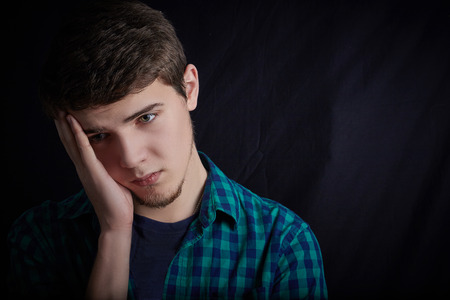 bothered: Stressed young student portrait, sad, bothered, holding hands on his head  isolated on black background.