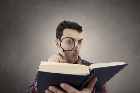 man holding book: Curious young student man holding book with a magnifying glass.Perplexed Young man student holding magnifying glass and a book isolated over grey background.