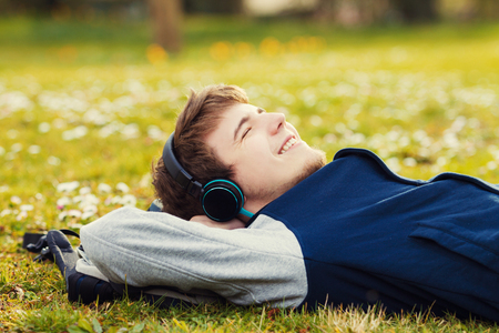 sleeping tablets: Young student, man relaxing smiling while lying on grass and listening to music.Player.Music,Relax