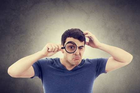 perplexed: Perplexed Young man student holding magnifying glass isolated over grey background. Stock Photo