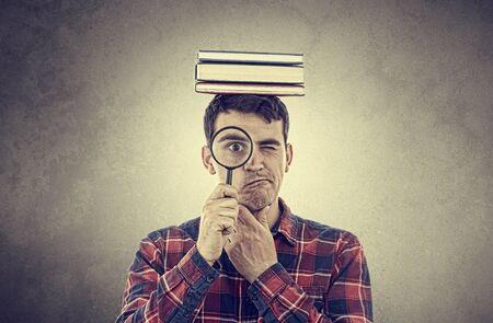 confundido: Estudiante de pensamiento hombre joven que sostiene una lupa y una pila de libros sobre la cabeza aisladas sobre gris background.Curious joven estudiante hombre sosteniendo libros con una lupa.