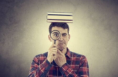 confused: Thinking Young man student holding magnifying glass and a  stack of books on head isolated over grey background.Curious young student man holding books with a magnifying glass. Stock Photo
