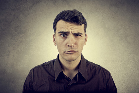 Disgusting expression.Portrait of disgusted man over grey background. Imagens