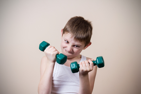 tired person: Angry little boy with dumbbell.Facial expression,Sport. Stock Photo
