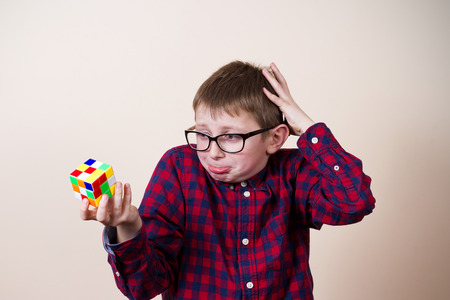 puzzling: Confused little boy nerd ,holding a puzzle cube and a hand on his head.Concept,perplexed.
