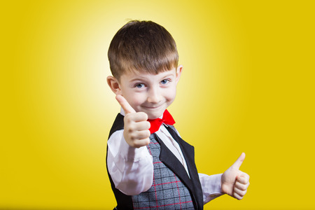 Portrait of happy little boy showing thumbs up gesture wearing costume and a red bow, isolated over yellow background.Funny,happiness.