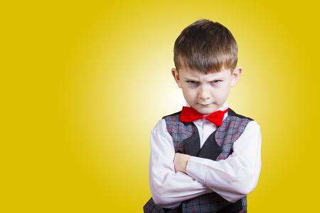 stubborn: Stubborn,sad,upset  little boy,child  isolated over yellow background.Facial expression