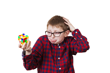 perplexed: Confused little boy nerd ,holding a puzzle cube and a hand on his head.Concept,perplexed.