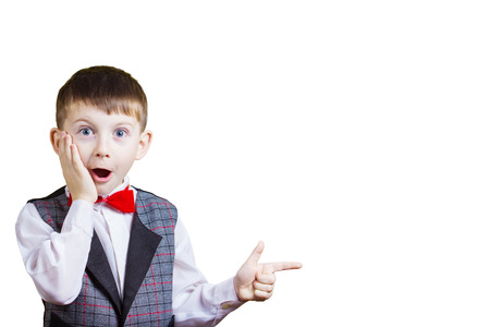 Surprised Pointing little boy isolated over yellow background. Standard-Bild