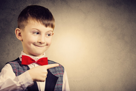 Smiling Pointing little boy isolated over grey background.