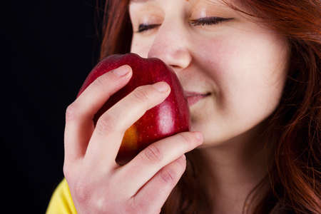 red bathrobe: Young woman holding and smelling a fresh red apple over black background.