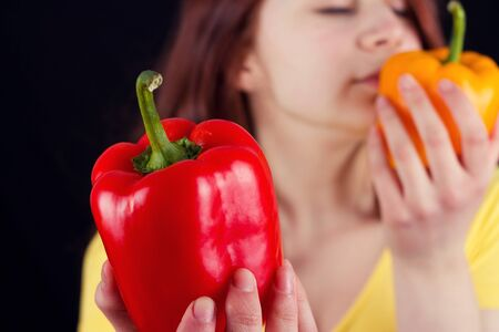 red bathrobe: Young woman holding and smelling a fresh red pepper over black background.