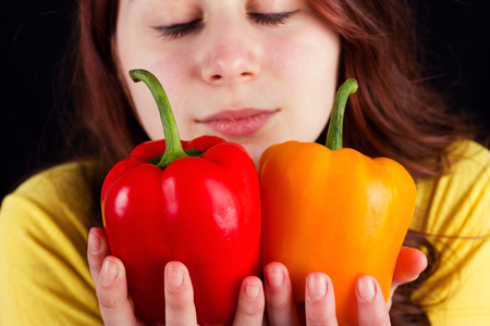 red bathrobe: Young woman  smiling and holding  a fresh red pepper over black background.Eat Raw