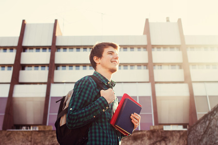 University.Smiling young student man holding a book and a bag on a university background .Young smiling student  outdoors Life style.City.Student. Stock Photo