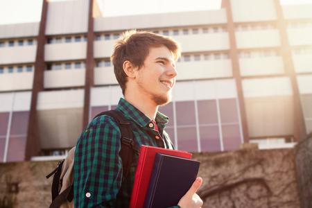 adolescentes estudiando: University.Smiling joven estudiante sostiene un libro y una bolsa sobre un fondo universitario .Young estudiante sonriente al aire libre Vida style.City.Student.